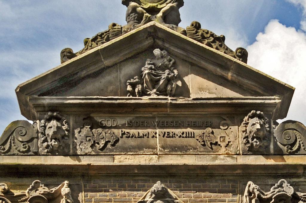 Het timpaan van het weeshuis in Leiden toont een personificatie van Caritas als moeder met kinderen
