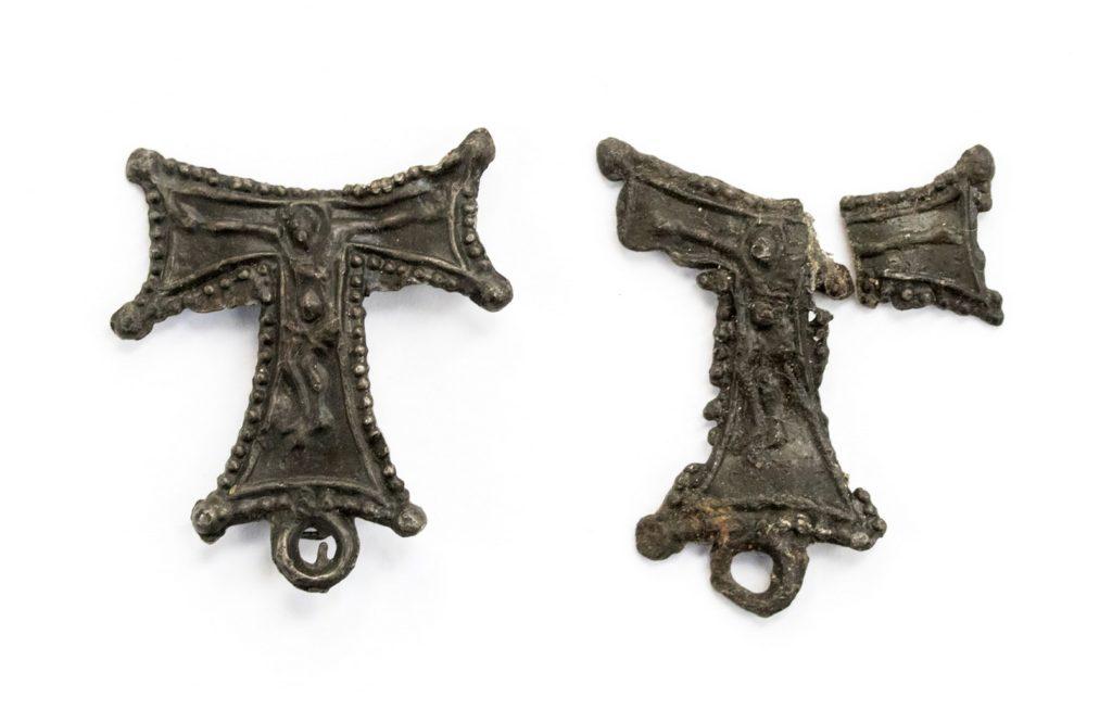 Twee loodtinnen draagtekens in de vorm van een letter Tau en daarop een gekruisigde Christusfiguur, oogjes aan de onderzijde